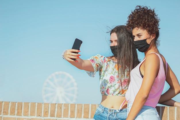 Glückliche junge mädchen, die selfies mit gesichtsmaske nehmen