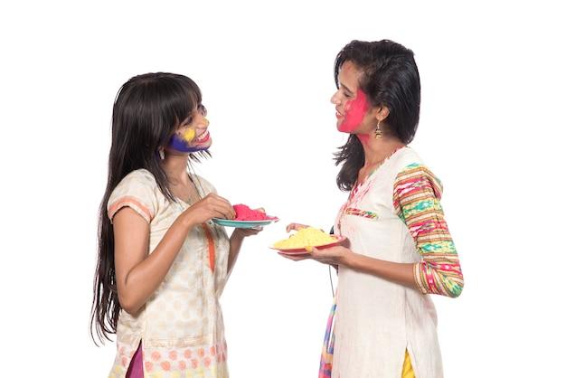 Glückliche junge mädchen, die spaß mit buntem puder am holi festival der farben haben
