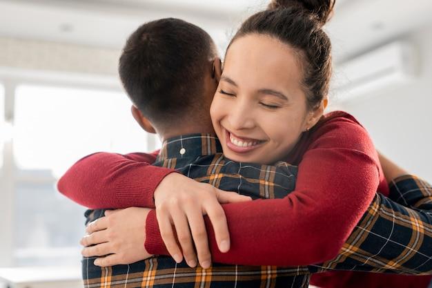 Glückliche junge mischlingsfrau, die ihren freund oder gruppenmitglied während der psychotherapie-sitzung umarmt