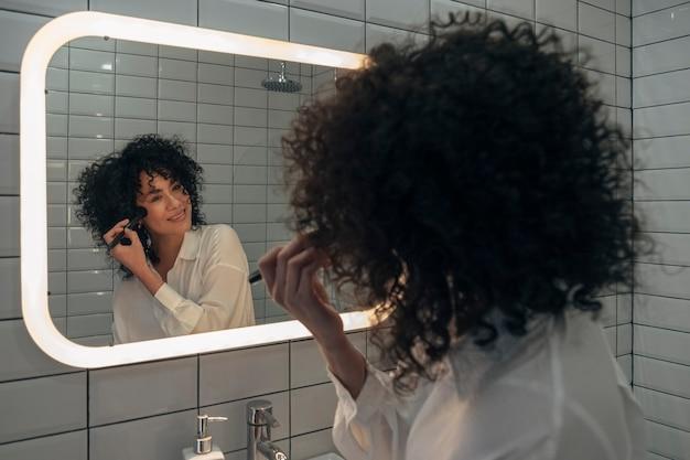 Glückliche junge mischlingsfrau, die im modernen waschraum make-up anwendet morgenroutinenkonzept schönheit