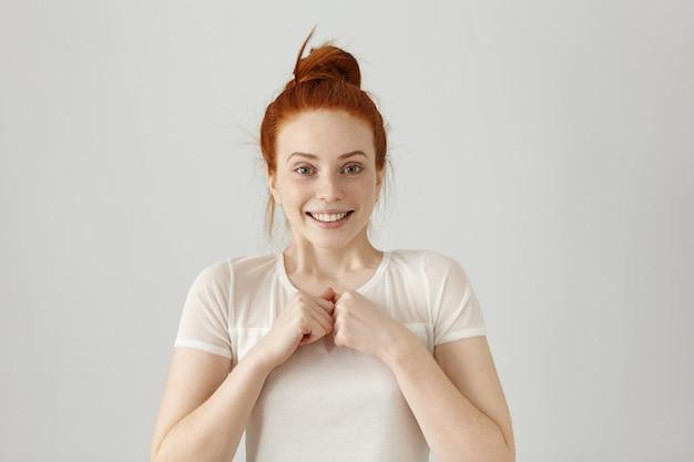 Glückliche junge mitarbeiterin freut sich über ihren erfolg bei der arbeit, lächelt breit und hält die fäuste geballt. schönes rothaariges mädchen in der bluse, die glücklich und aufgeregt fühlt