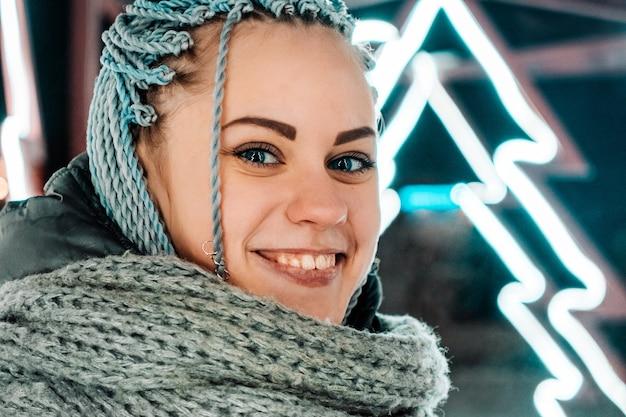 Glückliche junge moderne frau mit zöpfen oder dreadlocks, die lächelnd in die kamera vor dem hintergrund der fluoreszierenden beleuchtung schauen