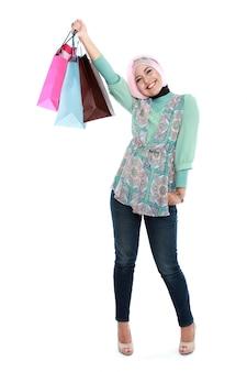 Glückliche junge muslimische frau mit einkaufstasche