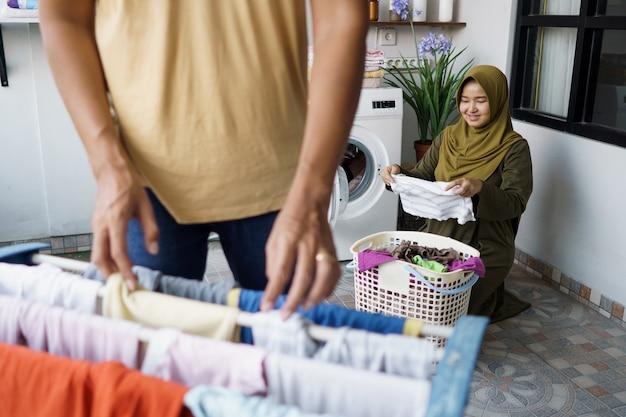 Glückliche junge muslimische frau und ihr mann, die wäsche zusammen zu hause machen
