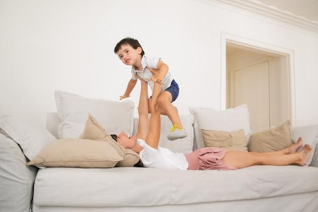 Glückliche junge mutter, die auf sofa liegt und mit sohn spielt.