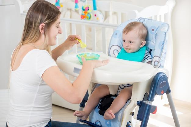 Glückliche junge mutter, die ihr baby mit fruchtsauce füttert