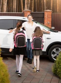 Glückliche junge mutter, die ihre beiden töchter nach der schule im auto trifft