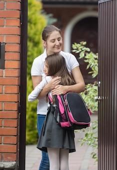 Glückliche junge mutter, die ihre tochter nach der schule vor dem haus trifft