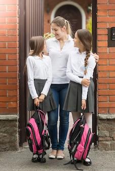 Glückliche junge mutter, die ihre töchter ansieht, die zur schule gehen