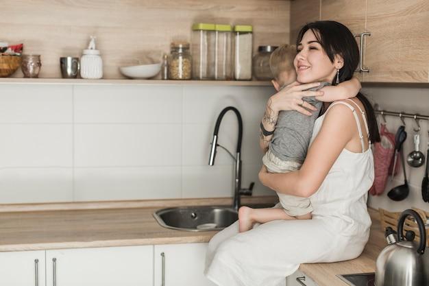 Glückliche junge mutter, die ihren sohn sitzt auf küchenarbeitsplatte trägt