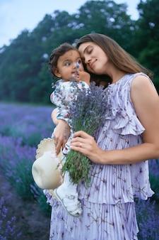 Glückliche junge mutter, die lavendelblumenstrauß und -kind hält