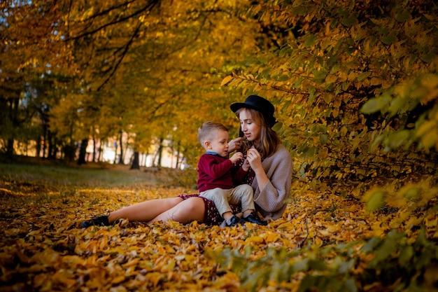 Glückliche junge mutter, die mit baby im herbstpark mit gelben ahornblättern spielt. familie, die im herbst draußen geht