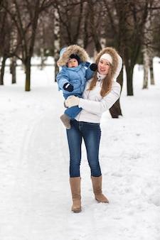Glückliche junge mutter, die mit ihrem baby im park im winter geht