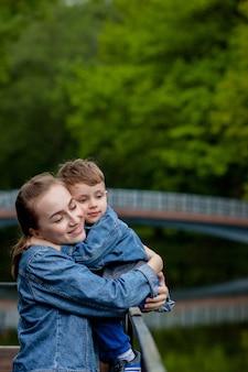 Glückliche junge mutter, die mit ihrem kleinen kleinen sohn am warmen frühling oder sommertag im park spielt und spaß hat