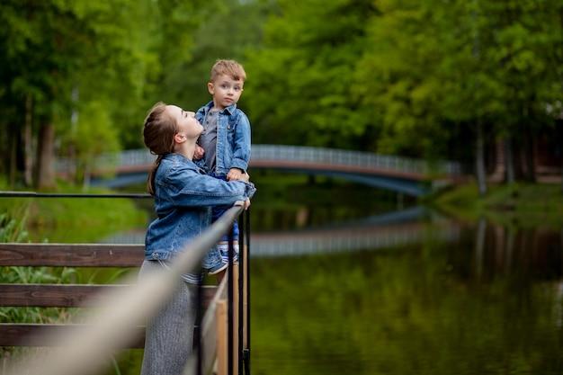 Glückliche junge mutter, die mit ihrem kleinen kleinen sohn am warmen frühlings- oder sommertag im park spielt und spaß hat. glückliches familienkonzept, muttertag Premium Fotos