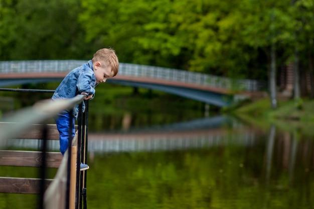 Glückliche junge mutter, die mit ihrem kleinen kleinen sohn am warmen frühlings- oder sommertag im park spielt und spaß hat. glückliches familienkonzept, muttertag