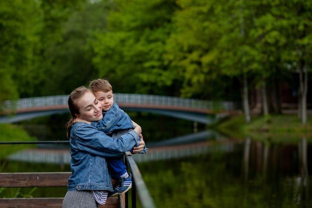 Glückliche junge mutter, die mit ihrem kleinen kleinen sohn am warmen frühlings- oder sommertag im park spielt und spaß hat. glückliches familienkonzept, muttertag.