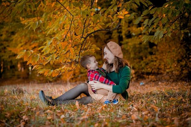 Glückliche junge mutter, die mit ihrem kleinen kleinen sohn am warmen herbsttag des sonnenscheins im park spielt und spaß hat. glückliches familienkonzept