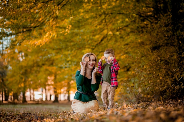 Glückliche junge mutter, die mit ihrem kleinen kleinen sohn am warmen herbsttag des sonnenscheins im park spielt und spaß hat. glückliches familienkonzept.