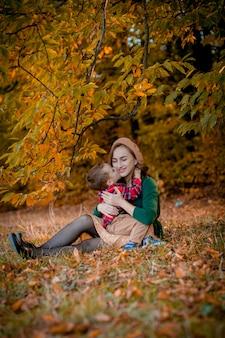 Glückliche junge mutter, die mit ihrem kleinen kleinen sohn am warmen herbsttag im park spielt und spaß hat