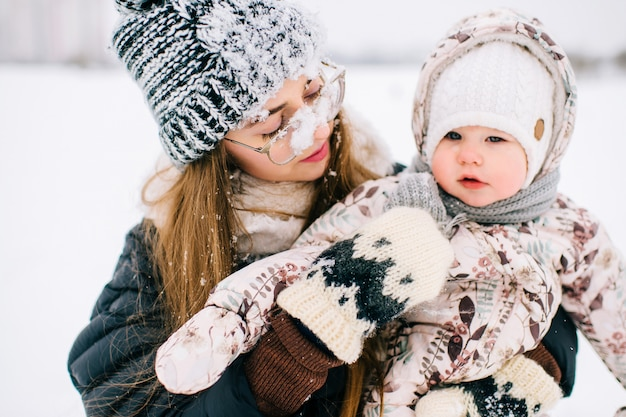 Glückliche junge mutter, die mit ihrem reizenden baby auf dem schneebedeckten gebiet des winters spielt.