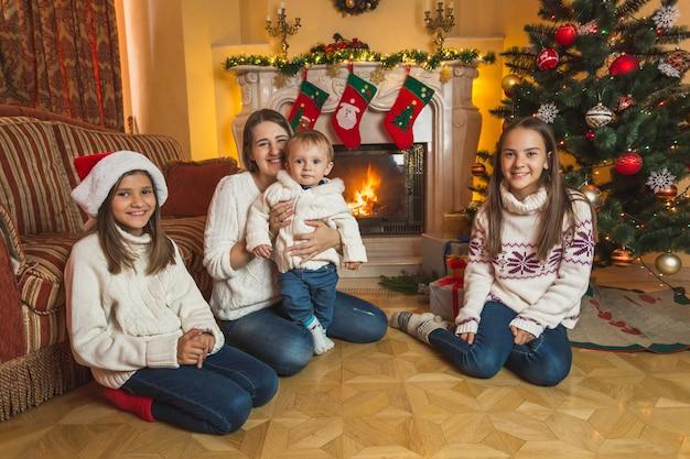 Glückliche junge mutter, die mit kindern auf dem boden am kamin sitzt. geschmückter weihnachtsbaum im hintergrund.
