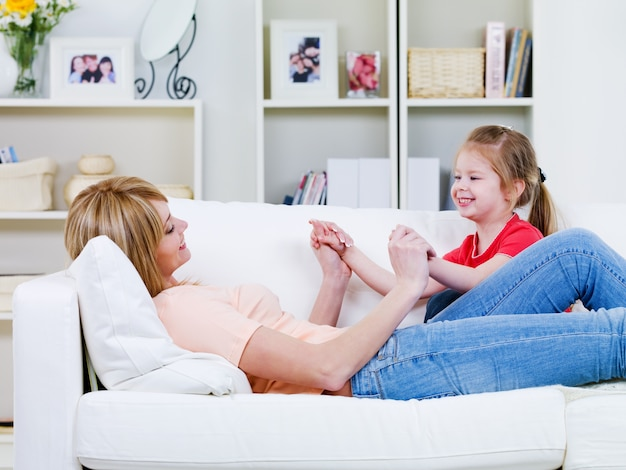 Glückliche junge mutter, die sich auf dem sofa entspannt und mit ihrer kleinen tochter spielt - drinnen