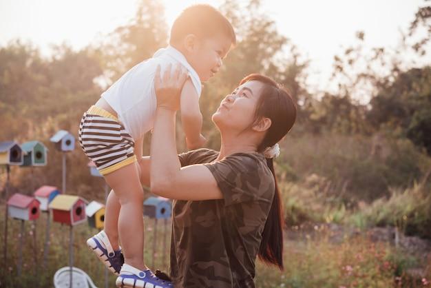 Glückliche junge mutter, die spaß mit ihrem kleinen babysohn im park an einem sonnigen sommertag spielt und hat