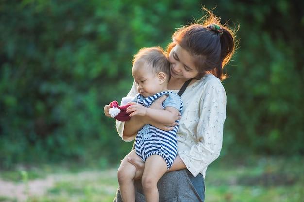 Glückliche junge mutter, die spaß mit ihrem kleinen babysohn spielt und hat