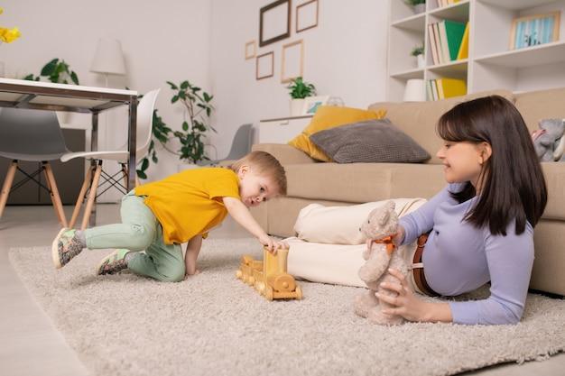Glückliche junge mutter, die zu hause auf weichem teppich liegt und spielzeugbär hält, während ihr sohn mit spielzeugeisenbahn spielt