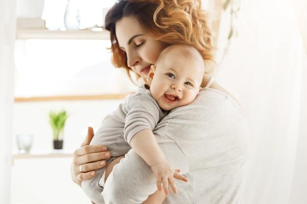 Glückliche junge mutter hält kostbares kleines kind und umarmt sanft seinen kleinen körper. kind, das freudig lacht und kamera mit großen grauen augen betrachtet.