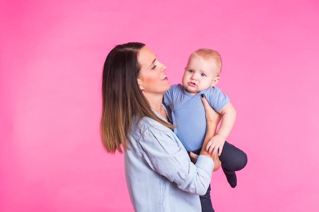 Glückliche junge mutter mit einem babykind auf rosa.