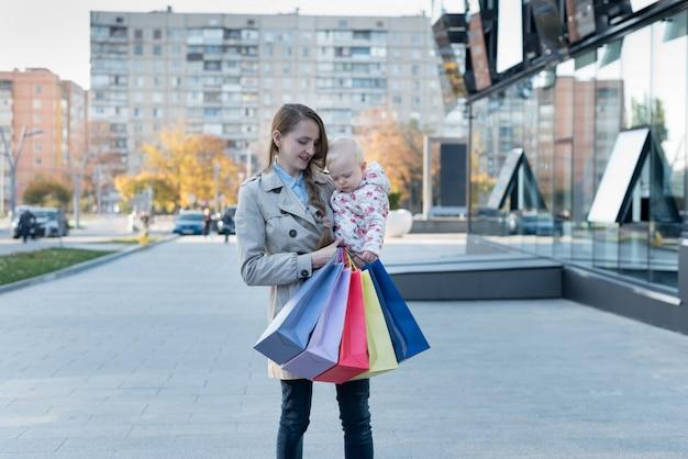 Glückliche junge mutter mit kleiner tochter auf den armen und den einkaufstaschen in der hand.