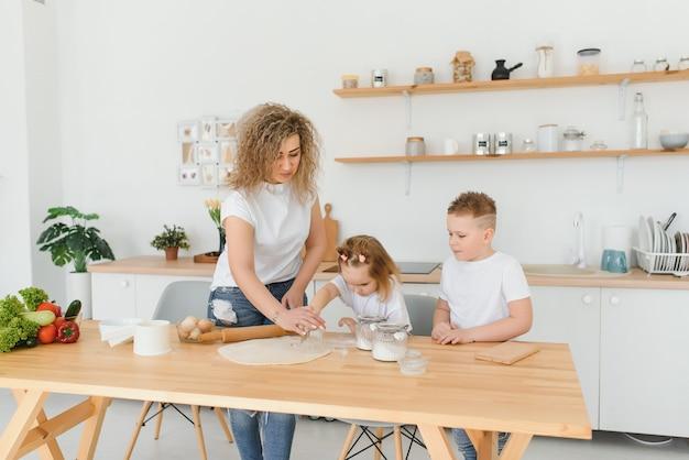 Glückliche junge mutter mit niedlichen kleinen vorschulkindern haben spaß, teigbackkuchen oder gebäck in der küche zusammen zu machen, überglückliche mutter lehren kleine kinder, die bäckerei kochen zu hause