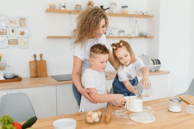 Glückliche junge mutter mit niedlichen kleinen vorschulkindern haben spaß, teigbackkuchen oder gebäck in der küche zusammen zu machen