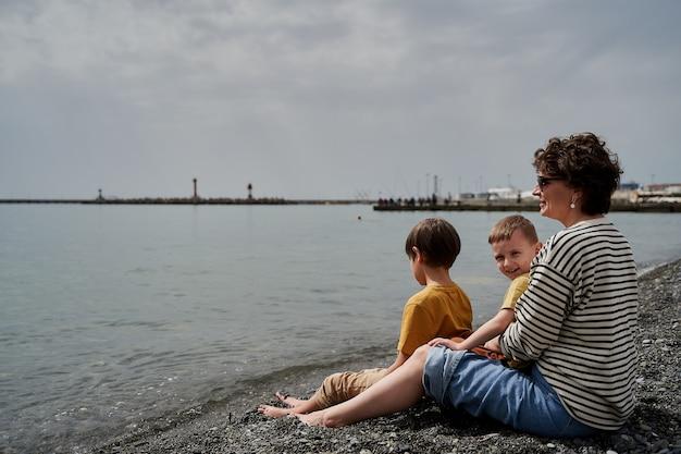 Glückliche junge mutter mit zwei kindern an der meeresküste.