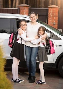 Glückliche junge mutter posiert mit töchtern, die rucksäcke neben dem auto tragen