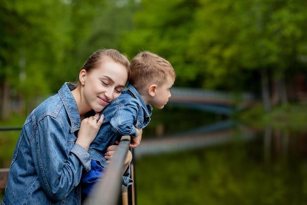 Glückliche junge mutter spielt und hat spaß mit ihrem kleinen kleinen sohn am warmen frühling oder sommertag im park.