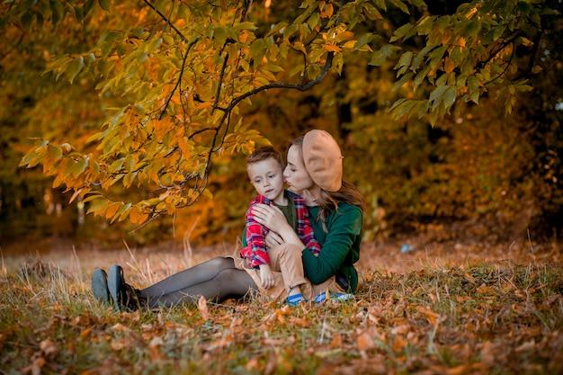 Glückliche junge mutter spielt und hat spaß mit ihrem kleinen kleinen sohn am warmen herbsttag des sonnenscheins im park