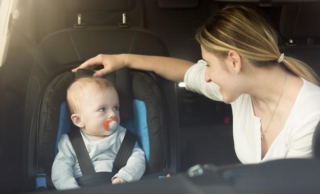 Glückliche junge mutter und baby im autokindersitz