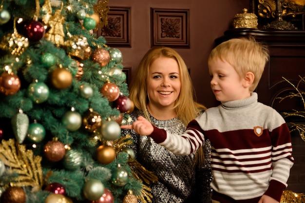 Glückliche junge mutter und ihr sohn zu hause mit einem weihnachtsbaum