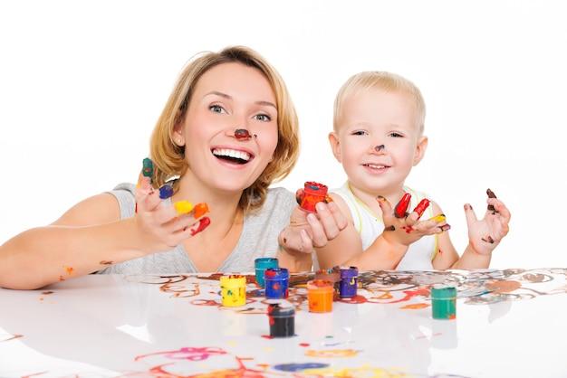 Glückliche junge mutter und kind mit gemalten händen lokalisiert auf weiß.