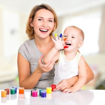 Glückliche junge mutter und kind mit gemalten händen