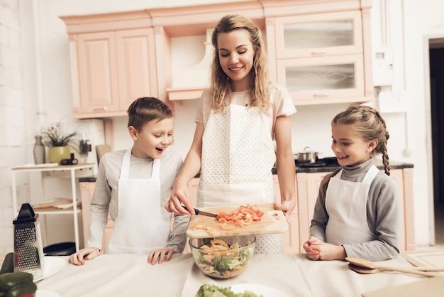 Glückliche junge mutter und kinder kochen mix hausgemachten salat.