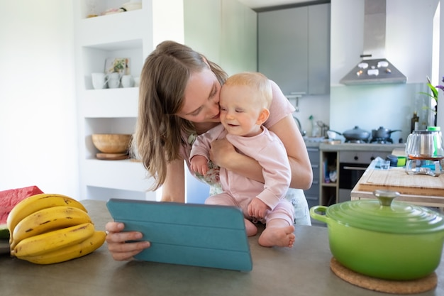 Glückliche junge mutter und kleine tochter, die tablette für videoanruf beim kochen zusammen in der küche verwenden. kinderbetreuung oder kochen zu hause konzept