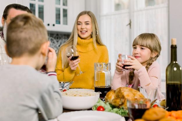 Glückliche junge mutter und niedliche kleine tochter, die gläser mit getränken am erntedankfesttisch hält