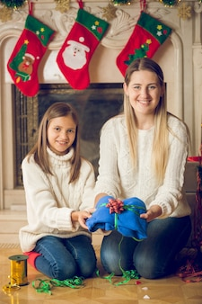 Glückliche junge mutter und tochter sitzen auf dem boden am kamin und packen pullover für weihnachten