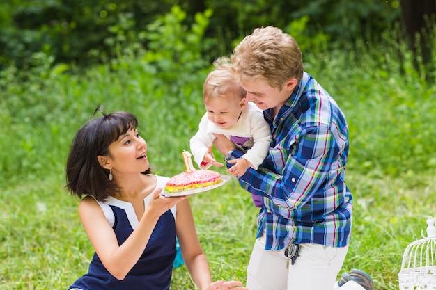 Glückliche junge mutter und vater mit ihrer kleinen tochter, die auf einer decke in einem park entspannt, der mit geburtstagstorte feiert.