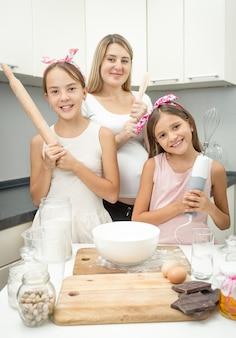 Glückliche junge mutter und zwei töchter, die mit küchenutensilien posieren