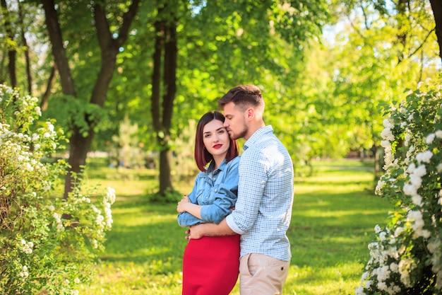 Glückliche junge paare am park, der am hellen sonnigen tag steht und lacht